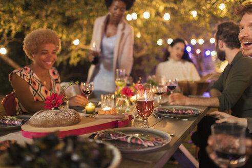 Friends enjoying candlelight dinner garden party - CAIF23265