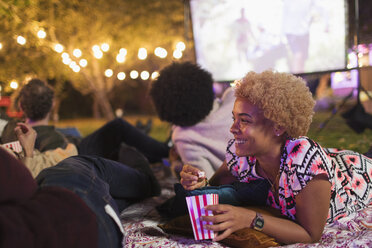 Happy woman eating popcorn, watching movie with friends in backyard - CAIF23268
