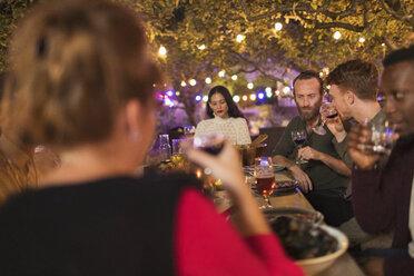 Friends drinking wine, enjoying dinner garden party - CAIF23271