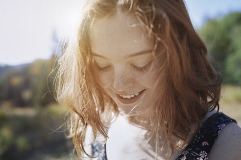 Smiling young woman with freckles looking down - CAIF23277