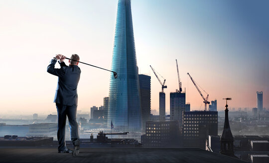 Businessman swinging golf club on city highrise rooftop - CAIF23283