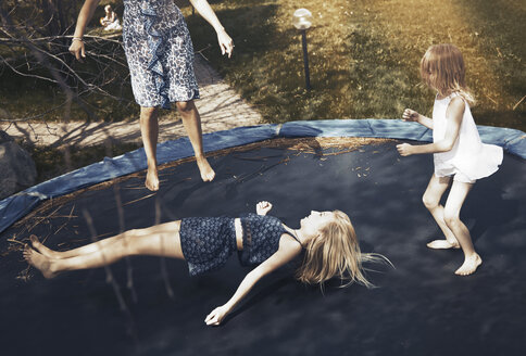 Happy family jumping on trampoline - CAIF23313