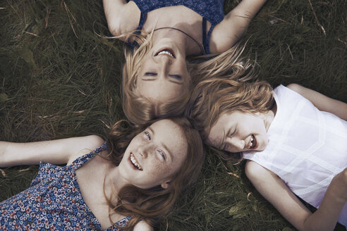 Portrait happy sisters laying in grass - CAIF23316