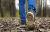 Sole of shoe of Caucasian boy walking on autumn leaves - BLEF00203