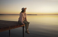 Caucasian woman sitting on dock of lake admiring sunset - BLEF00206