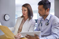Doctors discussing medical record in clinic - CAIF23371