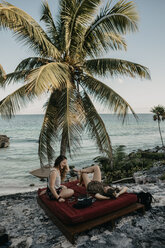 Mexico, Quintana Roo, Tulum, two happy young women relaxing on the beach - LHPF00662