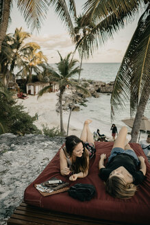 Mexico, Quintana Roo, Tulum, two happy young women relaxing on the beach - LHPF00668