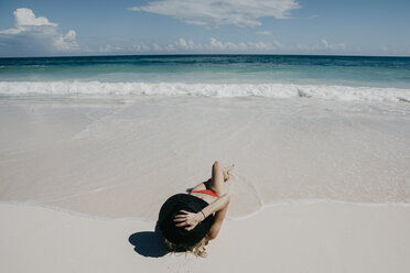 Mexico, Quintana Roo, Tulum, young woman with hat lying on the beach - LHPF00674