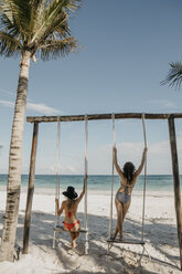 Mexico, Quintana Roo, Tulum, two young women on a swing on the beach - LHPF00677
