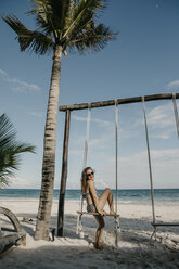 Mexico, Quintana Roo, Tulum, happy young woman on a swing on the beach - LHPF00680