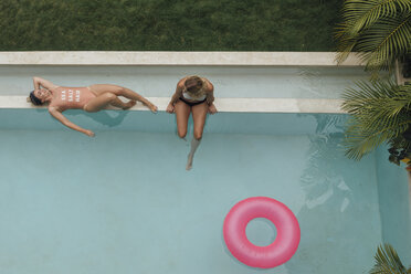 Two young women relaxing at swimming pool - LHPF00683