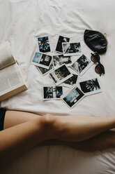Legs of young woman in bed with book and polaroid pictures - LHPF00692