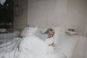 Happy young woman lying in bed - LHPF00698