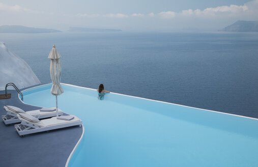 Caucasian woman in infinity pool admiring scenic view of ocean - BLEF00242
