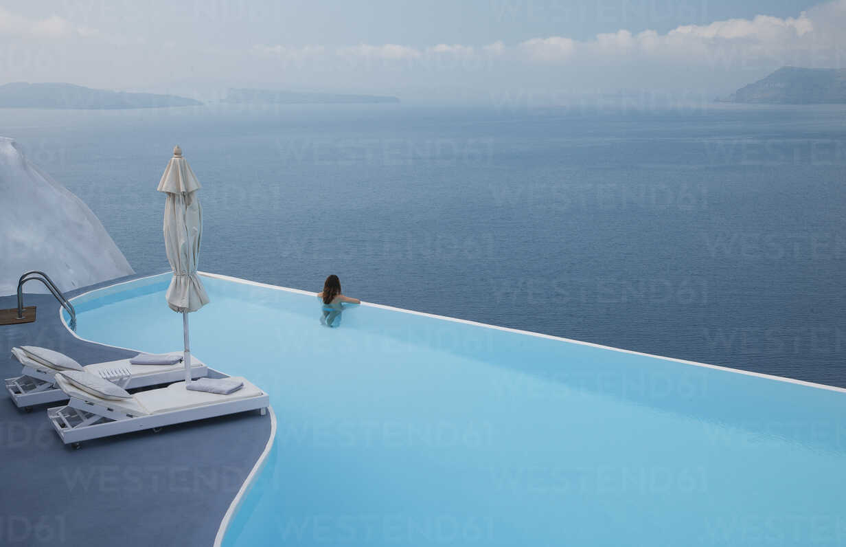Caucasian woman in infinity pool admiring scenic view of ocean - BLEF00242 - ac productions/Westend61
