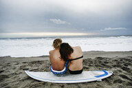Caucasian couple sitting on surfboard at beach - BLEF00257
