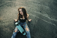 Caucasian teenage girl sitting on pavement with skateboard - BLEF00281