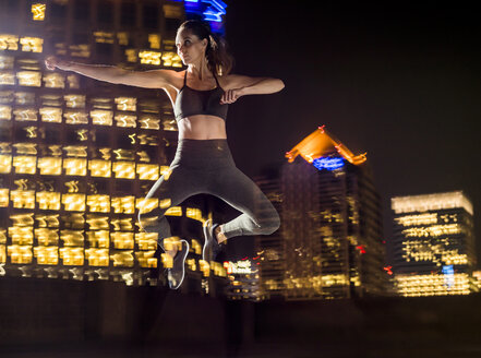 Double exposure of Caucasian woman jumping in city at night - BLEF00290