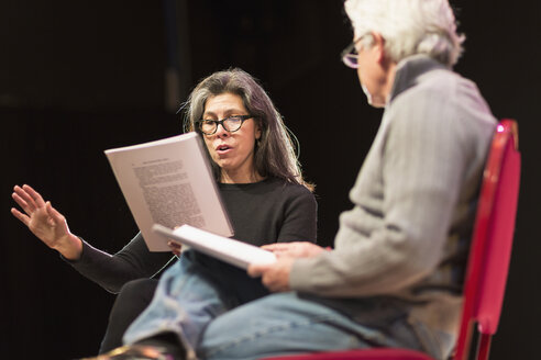 Hispanic man and woman reading scripts on theater stage - BLEF00317