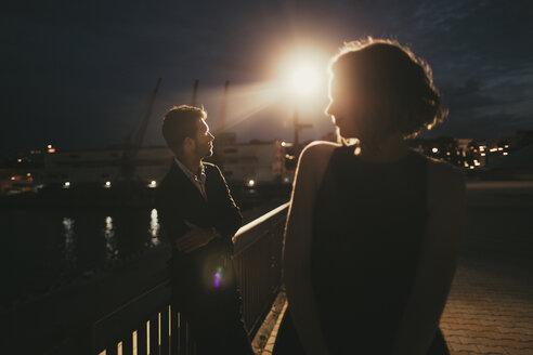 Caucasian man and woman at waterfront at night - BLEF00383