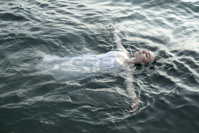 Caucasian woman wearing a dress floating in water - BLEF00395 - Alexey Karamanov/Westend61