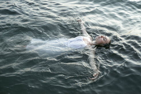 Caucasian woman wearing a dress floating in water - BLEF00395