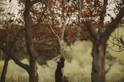 Caucasian woman standing in fog in forest - BLEF00404