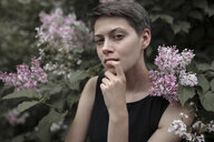 Curious Caucasian woman near flowering tree with finger on lip - BLEF00422
