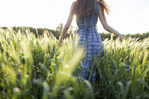Caucasian woman walking in field of tall grass - BLEF00446