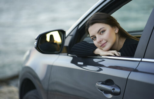 Smiling Caucasian woman leaning in car window - BLEF00494