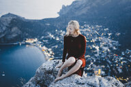 Caucasian woman sitting on rock near ocean - BLEF00620