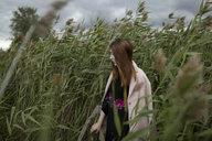 Asian woman standing in field of tall grass - BLEF00626