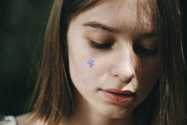 Caucasian woman with flower jewelry on cheek - BLEF00743