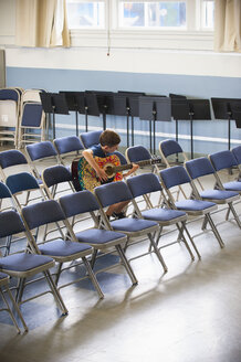 Caucasian boy sitting in row of chairs practicing guitar - BLEF00794