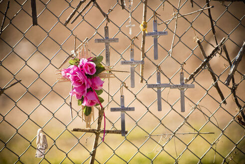 Crucifixes and flowers hanging on memorial fence - BLEF00842