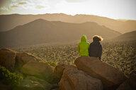 Boys sitting on rock admiring desert landscape - BLEF00851