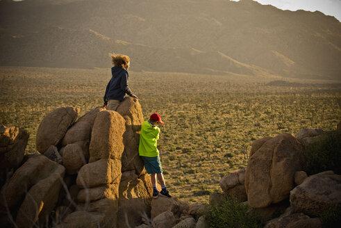 Boys standing on rocks admiring desert landscape - BLEF00857