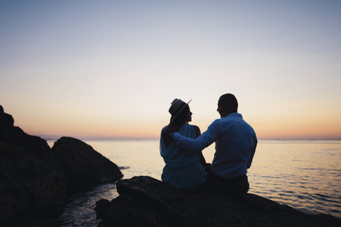 Silhouette of Caucasian couple sitting on rock near ocean at sunset - BLEF00932