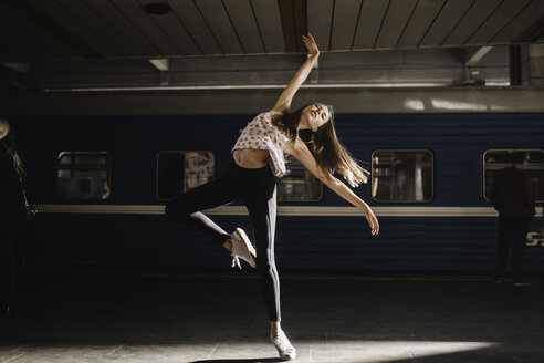 Caucasian woman dancing near train - BLEF00938