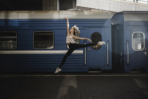 Caucasian woman dancing near train - BLEF00941