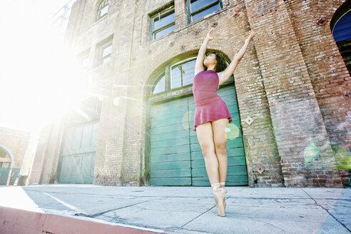 Sunbeams on mixed race woman dancing in city - BLEF00959