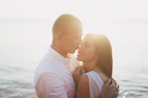 Caucasian couple hugging near ocean at sunset - BLEF01043