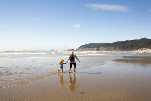 Caucasian family holding hands and running on beach - BLEF01052