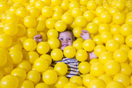 Caucasian girl laying in pile of yellow balls - BLEF01073