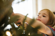Caucasian girl hanging lights on Christmas tree - BLEF01094