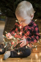 Caucasian baby boy sitting on floor wrapped in string lights - BLEF01097