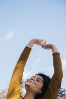 Wind blowing hair of Caucasian woman with arms raised - BLEF01112