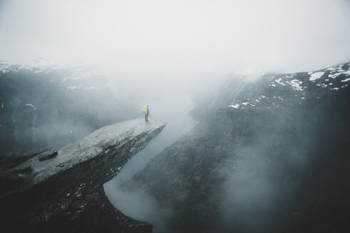 Caucasian man on foggy cliff admiring scenic view of mountain river - BLEF01130