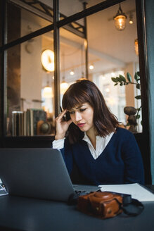 Businesswoman working at desk while using laptop in creative office - MASF11889